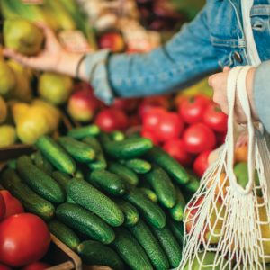 Close-up of woman holding an ecologically friendly reusable bag grabbing fruit and vegetables at a farmers market